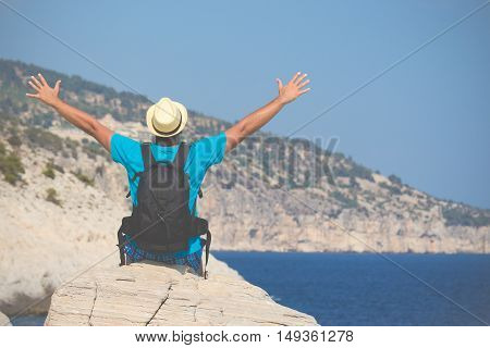 Rear view of young tourist guy sitting on the rock with hands up and enjoying the sea view