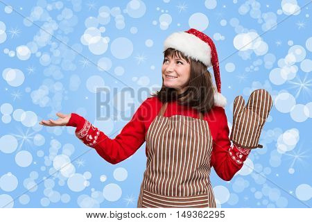 Portrait of attractive girl in chef apron oven glove and christmas hat showing pointing on copyspase for your text on holiday background.