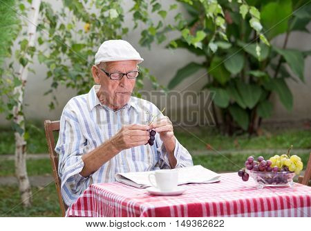Senior Man Eating Grape