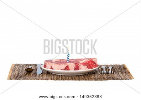 Raw beef steak on white background with Happy birthday candle
