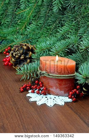 The branches of spruce and burning candle on grandma crocheted napkins. Christmas Composition Fir Tree Toys with Burning Candlesred berries crocheted doily Pine ConesBranches of Spruce on Wooden Background.