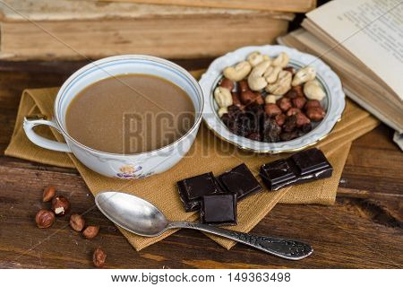 Cup of coffee with dry fruits and chocolate on a napkin
