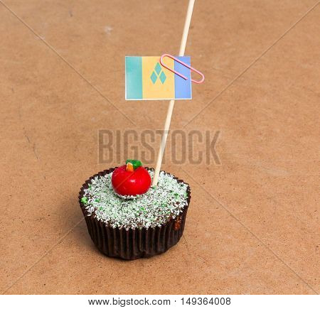 Flag of a st. vincent and the grenadines. Apple Cupcake with red apple shape bonbon on the top