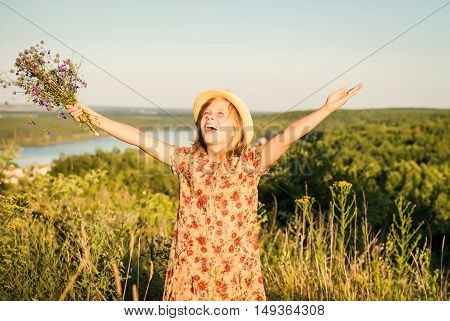 Portrait of happy girl in the summer meadow with arms raised to the sun. Freedom wellness and childhood concept.
