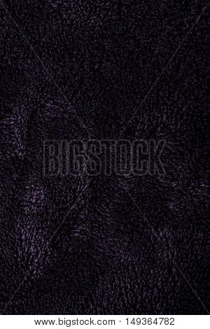 Vertical texture photo of dark black blanket. The surface is little bit shiny which make few reflections with lighter grey color of surface.