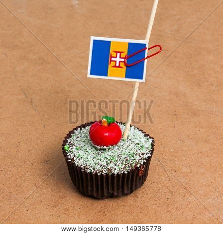 Flag of Madeira archipelago. Apple Cupcake with red apple shape bonbon on the top