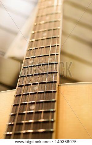 Guitar neck. Metal strings. Shallow depth of field