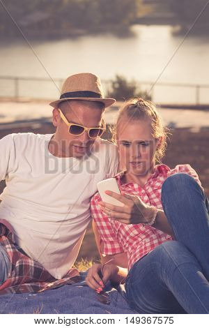 Beautiful young couple looking at the mobile smart phone together while sitting on the top of the hill.