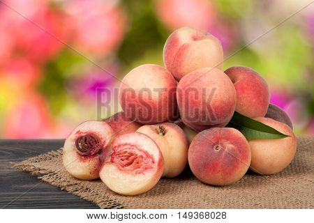heap of peaches on a wooden table with a blurred background.