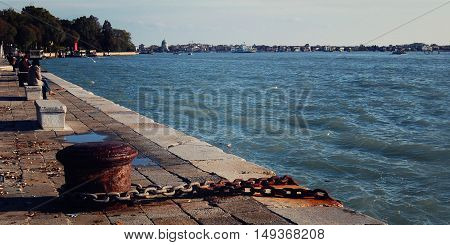 Old metal pillar and rusty anchor chain. Embankment in Venice. View on the Gulf of Venice.