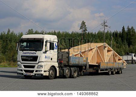 ORIVESI, FINLAND - SEPTEMBER 1, 2016: White MAN TGX 26.480 semi truck transports roof truss on flat trailer.