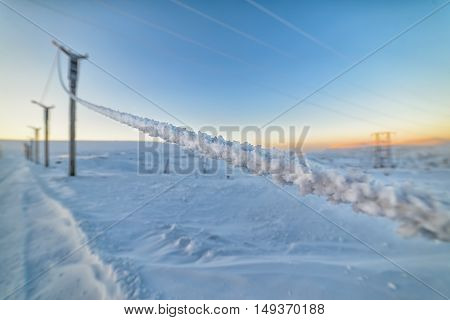 Electric mast lighting wire, covered with a thick layer of frost.