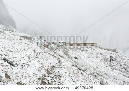 Thorong La, Nepal - October 15: Sherpa delivering supplies to high altitude base camp at 4540 m in snow blizzard, on October 2015 in Thorong La, Nepal.