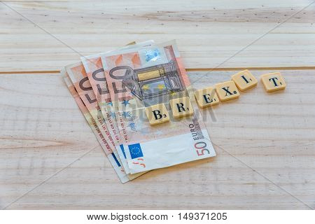 London UK - June 12 2016: Brexit text with euro money on wooden background. The United Kingdom European Union membership referendum on 23 June 2016