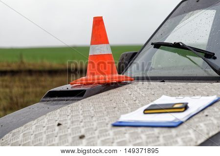 Orange traffic cone with white stripe on the hood of a road service vehicle. Clipboard Pad Paper Holder Clip and phone on blurred foreground. Shallow focus.