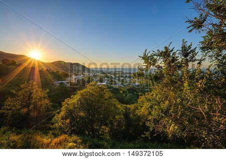 Aerial view of Ischia Island, Italy. Sunset: star sun with beams over hills and town