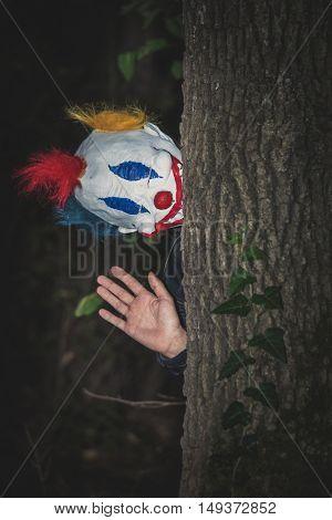 scary clown behind tree wave gesture