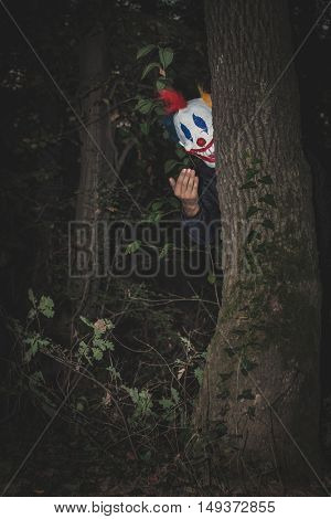 scary clown behind tree inviting with hand gesture night scene
