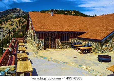 September 26, 2016 in Mt Baldy, CA:  Outdoor courtyard patio seating with a barbecue pit creating a rustic vibe at the Mt Baldy Notch Lodge where people can relax and dine surrounded by incredible mountain scenery taken in Mt Baldy, CA