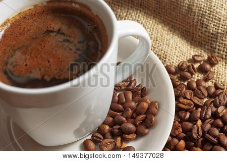 Closeup cup of coffee and coffee beans on jute background.