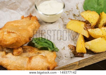 Fish in batter with potatoes lying on the paper in a wooden box closeup