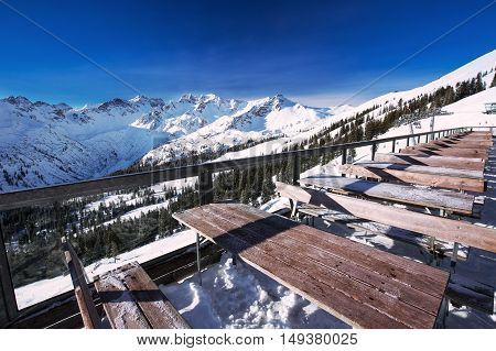 Tables on terrace covered by fresh snow near ski slopes on the top of Fellhorn Ski resort Bavarian Alps Oberstdorf Germany