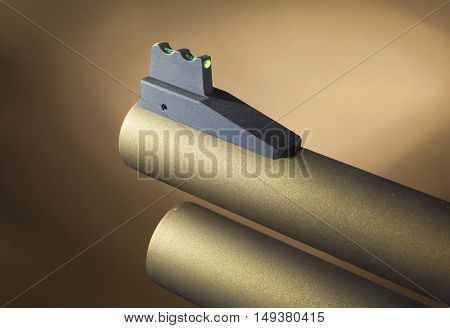 Fiber optic front sight on the barrel of a gold colored shotgun