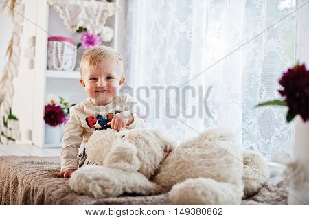 Cute Caucasian Baby Boy Sitting On Windowsill With Soft Toy Dog