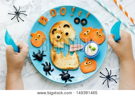 Creative idea for Halloween kids breakfast or snack. Funny monster toast with pumpkin olive spiders and white ghost sauce. Concept of healthy meal food for children top view