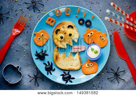 Creative idea for Halloween kids breakfast or snack - funny monster toast with pumpkin olive spiders and white ghost sauce. Concept of healthy meal food for children