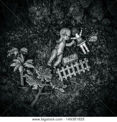 Two old dirty dolls and other toys lying on the ground, black and white version