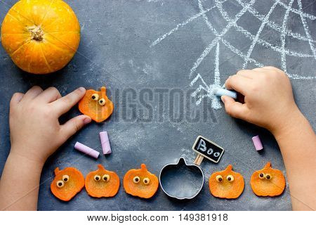 Happy halloween! Child draws with chalk spider web on the table with pumpkins. Kids preparing for Halloween