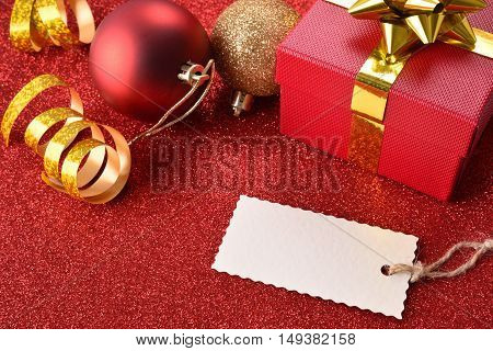 Xmas Decoration With Tag Gift Balls On Red Table Elevated