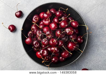 Fresh ripe black cherries in a black bowl on a grey stone background Top view.