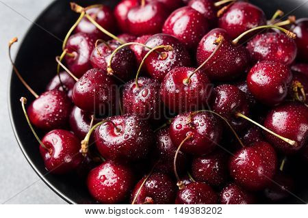 Fresh ripe black cherries in a black bowl on a grey stone background Close up.