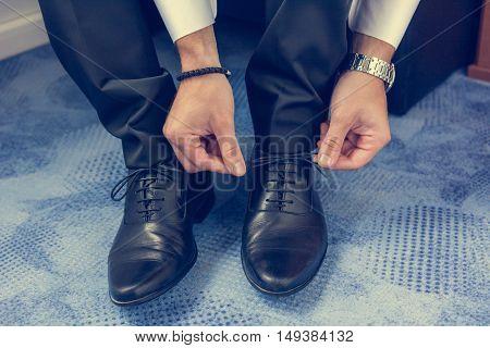 Groom tying shoelaces. Final wedding preaprations closeup.