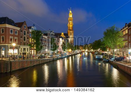 Night city view of Amsterdam canal and Westerkerk church, Holland, Netherlands.