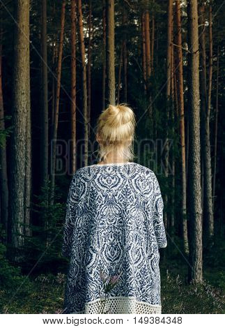 Young blonde woman in poncho standing in the woods with her back to the camera. Relaxed lifestyle.