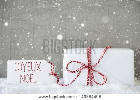 Label With French Text Joyeux Noel Means Merry Christmas. One Christmas Present On Snow. Cement Wall As Background With Snowflakes. Modern And Urban Style. Card For Birthday Or Seasons Greetings.