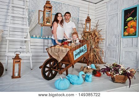 Young Caucasian Happy Family In Love Background White Wooden Room With Wheelbarrow And Pumpkin Decor