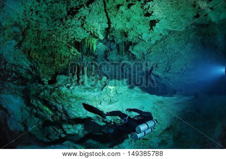 A lonely diver is swimming along the cave wall, Kukulkan cave, Yucatan peninsula, Mexico
