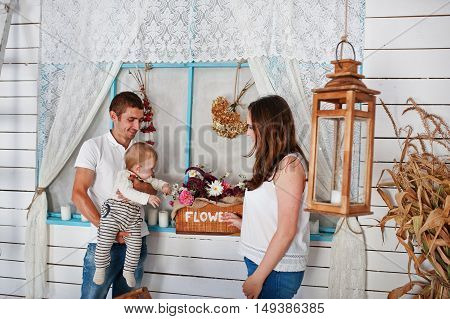 Young Caucasian Happy Family In Love Background White Wooden Room With Decor