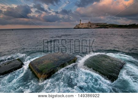 El Morro fortress in Havana bay entrance at sunset with waves splashing on rocks