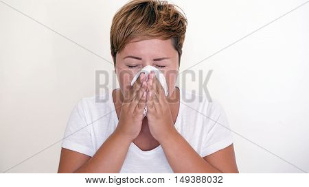 Short haired woman blowing her nose on the white background. Seasonal diseases. Allergies. Cold in the head. Selective focus.