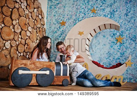 Young Happy Family With Son Playing In Decor Room With Children Wooden Locomotive