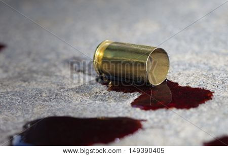 Pistol brass and blood that are on some concrete