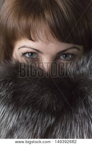 Expressive eyes of a young girl in natural fur collar
