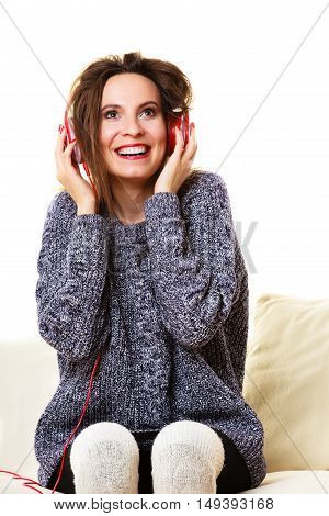 People leisure relax concept. Woman casual style red big headphones listening music mp3 sitting on couch at home relaxing