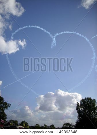 Royal Air Force Red Arrows aerobatic display team in flight creating a heart with an arrow through it in white smoke. Background of blue sky with white clouds and trees beneath.