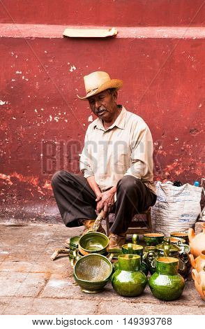 OAXACA MEXICO- DECEMBER 7, 2015: Old man selling typical handicraft pottery in a market in Oaxaca on December 7, 2015, Mexico.